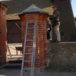Prace  przy  odrestaurowaniu   filarów  bramowych